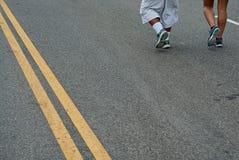 Una coppia che corre giù il boulevard del porto durante conquista la corsa del ponte immagine stock