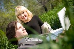 Una coppia che lavora al computer portatile in natura sull'erba Fotografia Stock Libera da Diritti