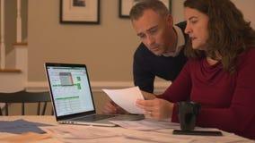una coppia che lavora con il loro debito video d archivio