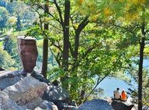 Una coppia che si siede su sopra un lago. Immagine Stock Libera da Diritti