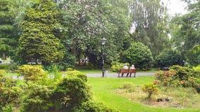 Una coppia che si siede su un banco di parco a Southampton fotografia stock libera da diritti
