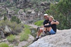 Una coppia che si siede su una scogliera. Fotografie Stock Libere da Diritti