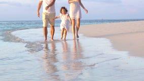 Una coppia con un piccolo bambino che cammina una spiaggia Movimento lento stock footage