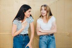 Una coppia di belle amiche contro un fondo giallo della parete Immagine Stock