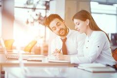 Una coppia di colleghi allo scrittorio in ufficio soleggiato fotografia stock libera da diritti