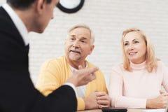 Una coppia di gente anziana è venuto ad una consultazione con un avvocato L'avvocato comunica con un uomo e una donna Immagine Stock