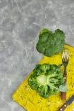 Una coppia di germogli di insalata sana sono sul bordo giallo Broccolo verde fresco genere verticale di fiore di verdure verde Sa fotografia stock libera da diritti