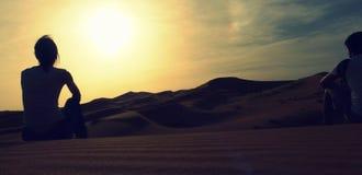 Una coppia di giovani avventurieri che si siedono sopra una duna di sabbia e che godono di un tramonto stupefacente sopra il mare Immagini Stock Libere da Diritti