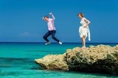 Una coppia di nozze che salta nell'oceano Immagini Stock