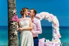 Una coppia di nozze su una spiaggia soleggiata Immagini Stock Libere da Diritti