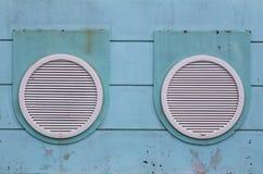 Una coppia di oblò su una parete verde Fotografie Stock