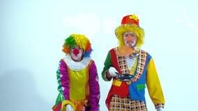 Una coppia di pagliacci di circo che giocano con i pancake e le padelle stock footage