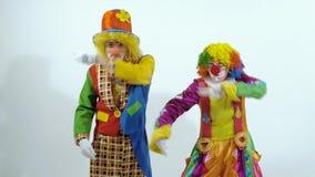 Una coppia di pagliacci variopinti stanno ballando un ballo divertente che mostra le emozioni di festa stock footage