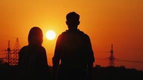 Una coppia di turisti che ammirano il tramonto sopra la città, retrovisione immagini stock libere da diritti