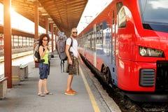 Una coppia di turisti di viaggiatore con zaino e sacco a pelo che aspettano per imbarcarsi su un treno Fotografie Stock