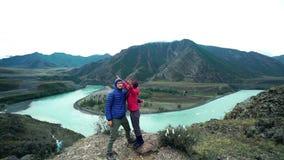 Una coppia di turisti stanno stando sopra una montagna di pietra, divertendosi ed abbracciando, un fiume veloce della montagna sc video d archivio