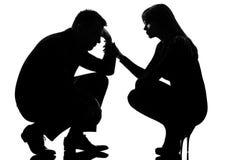 Una coppia equipaggia la consolazione preoccupantesi della donna e triste immagini stock