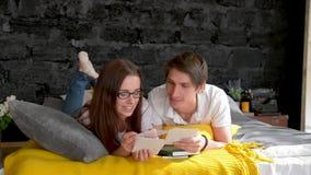 Una coppia esamina le foto di famiglia, a casa sul letto archivi video