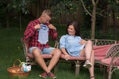 Una coppia eterosessuale nel giardino gode di di aspettare la nascita immagini stock