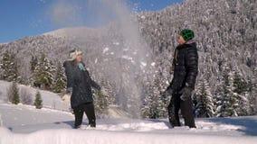 Una coppia felice degli amanti cammina attraverso la foresta che innevata gettano la neve e la risata Il tipo e la ragazza sono archivi video