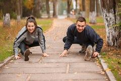 Una coppia felice sta preparandosi in un parco di autunno Faccia l'allungamento delle gambe all'esterno Fotografia Stock
