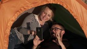 Una coppia felice in una tenda sta guardando qualcosa sul telefono e sulla risata archivi video