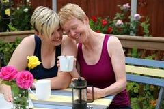 Una coppia gay felice a casa nel giardino ed abbracciare immagini stock libere da diritti