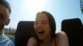 Una coppia gli amanti guida il waterslide in un parco di divertimenti Umore di estate, viaggiante La ragazza ed il sorriso del ti video d archivio
