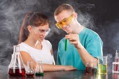 Una coppia i chimici esamina una boccetta con un liquido verde Il concetto di scienza Fotografia Stock