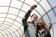Una coppia i giovani con differenti colori della pelle cammina intorno alla città e fa un video di se stessi sull'azione fotografia stock libera da diritti