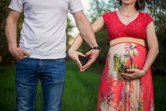 Una coppia incinta felice fatta dalle mani fatte di un cuore immagine stock libera da diritti