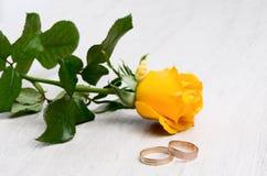 Una coppia le fedi nuziali e la rosa di giallo immagini stock