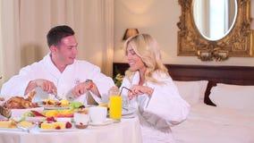 Una coppia in loro accappatoi pranza all'hotel video d archivio