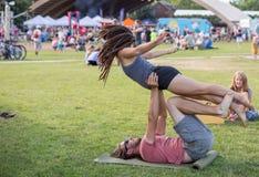 Una coppia nel parco pratica il arcayoga durante il mercato degli agricoltori Fotografia Stock Libera da Diritti
