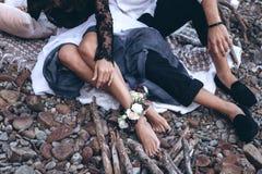 Una coppia nell'amore sta sedendo sulla spiaggia con i fiori fotografia stock libera da diritti