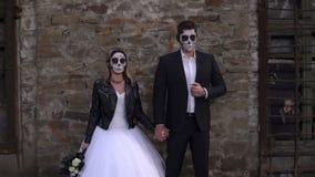 Una coppia orribile con trucco per il supporto di Halloween contro un vecchio muro di mattoni video d archivio