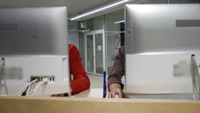 Una coppia positiva sta scherzando quando lavora nell'ufficio archivi video