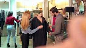 Una coppia sceglie i vestiti nel deposito, essi esamina il cappotto sul manichino video d archivio