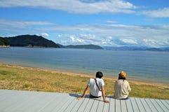 Una coppia si siede sulla piattaforma e gode della vista del mare fotografia stock libera da diritti