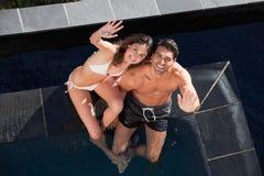 Una coppia sorridente che fluttua alla macchina fotografica Immagine Stock
