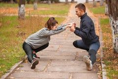 Una coppia sta facendo gli sport nel parco nella caduta Tenersi per mano dei muscoli di allungamento Fotografia Stock