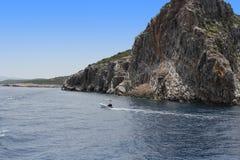 Una coppia sta navigando su un yacht lungo una riva rocciosa Fotografia Stock Libera da Diritti