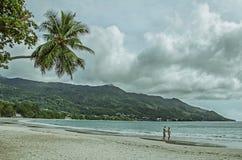 Una coppia sulla spiaggia piacevole con la sabbia bianca, le palme e le colline verdi Immagine Stock
