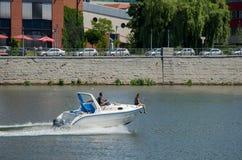 Una coppia in un'imbarcazione a motore nel fiume La donna si siede sul rostro della a immagini stock