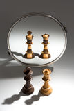 Una coppia un re nero e una regina bianca sta guardando in uno specchio per vedersi come un paio colorato in bianco e nero Immagini Stock Libere da Diritti