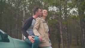 Una coppia - un tipo e una ragazza sono stare, appoggiantesi un'automobile nella foresta che stanno sorridendo, il tipo sta bacia stock footage
