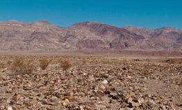 Una cordillera distante en California sobre un desierto rocoso Fotos de archivo