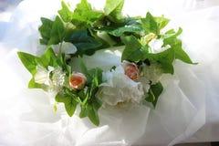 Una corona dei fiori bianchi e delle foglie verdi su un fondo bianco Immagine Stock