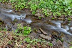 Una corrente veloce in terreno montagnoso Acqua che entra nel fiume indicato in un'esposizione lunga immagine stock libera da diritti