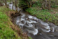 Una corrente veloce in terreno montagnoso Acqua che entra nel fiume indicato in un'esposizione lunga immagine stock